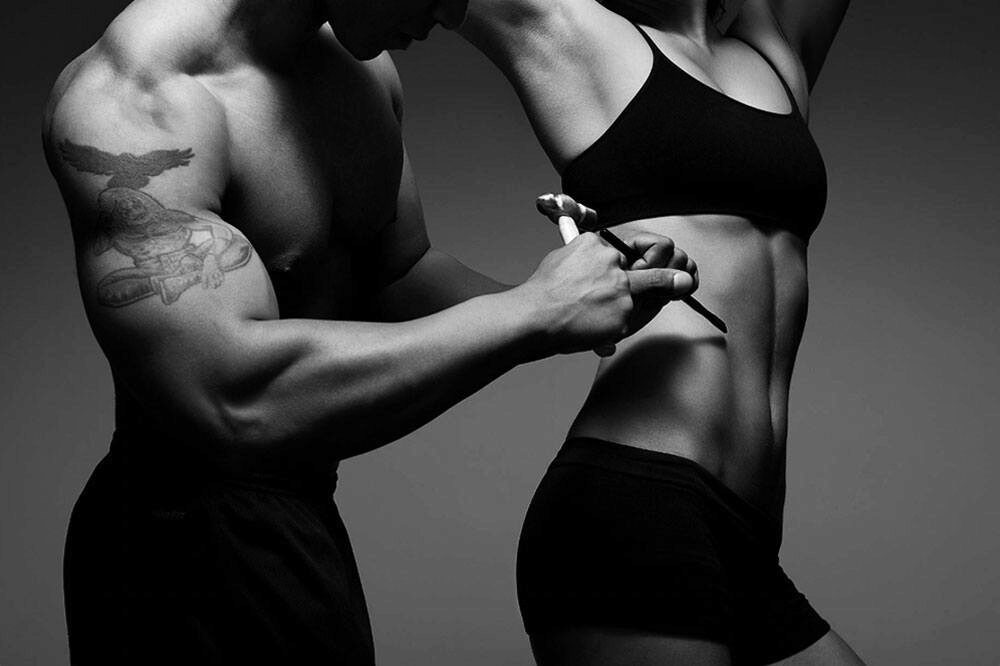 fit man is sculpting a woman's belly